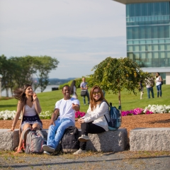 Students sitting on stone benches outside of University Hall