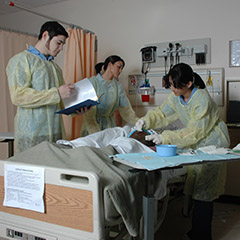 Nursing students in scrubs practice on a mannequin in a hospital room