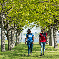 Two students walking through trees on campus