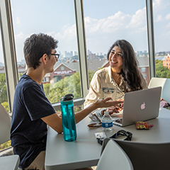 Two students in new dorms sitting at table looking at laptop