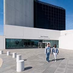 Two students walking in front of the JFK Library.