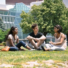 A group of three students sitting together on the grass in front of the Integrated Sciences Complex building at UMass Boston.