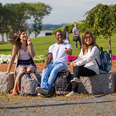 three students on stone benches outside on campus