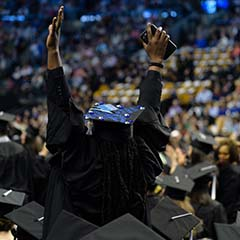 Student in cap and gown at graduation with hands in the air