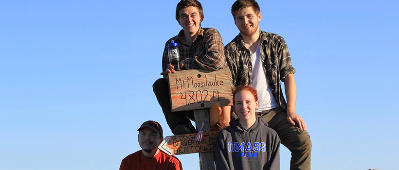 Four students posing around a sign at the top of a mountain