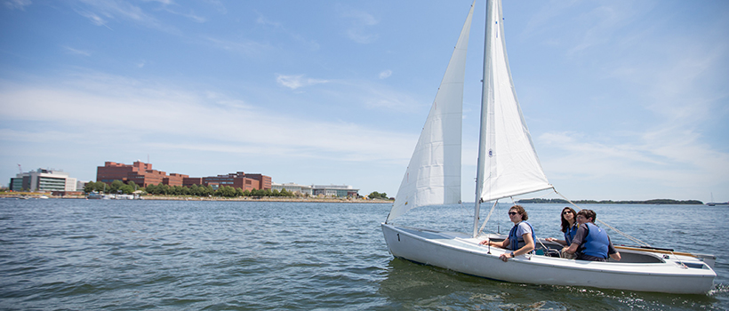 Several students riding in a sailboat on the water in the harbor with UMass Boston buildings visible in the background