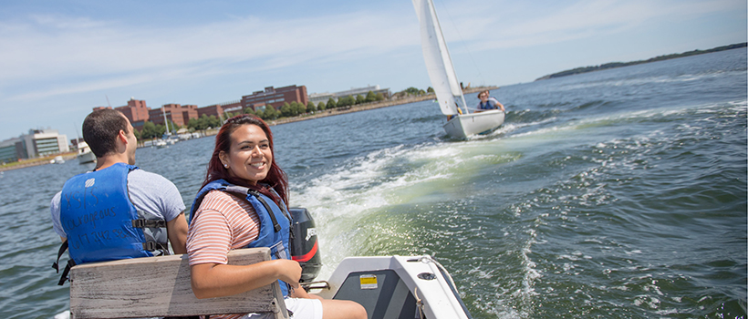A male and female student on a sailboat on the water in front of UMass Boston