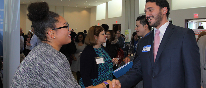 A student in a suit shakes hands with a woman at a booth at a UMass Boston career fair