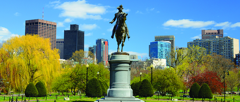 Statue in front of Boston City skyline in Boston Common