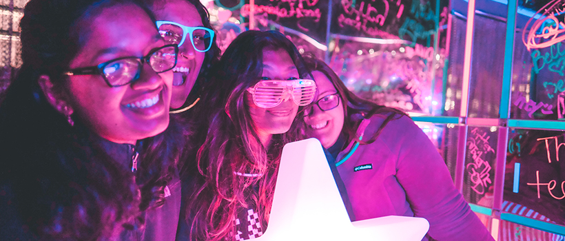 Four students posing for a photo wearing glowing sunglasses, holding glowing star