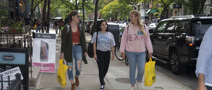 Three students walking along the sidewalk on Newbury Street in Boston